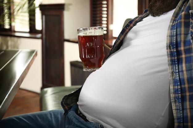パブで彼の大きな腹にビールのガラスを保持している男