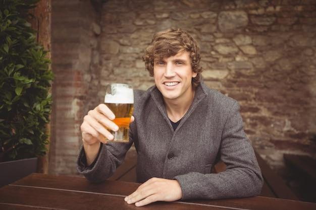 Мужчина держит стакан пива