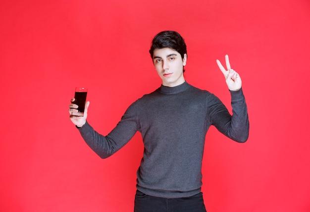 Uomo che tiene un bicchiere di succo rosso e si sente soddisfatto