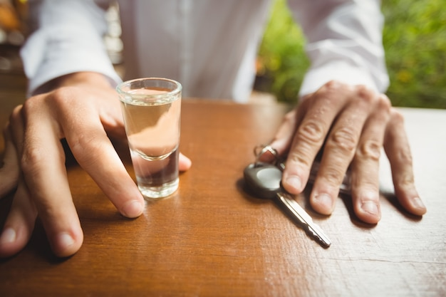 Man holding glass of tequila shot and car key in bar counter