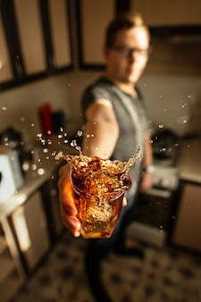 A man holding a glass of whiskey with splashes in the kitchen.