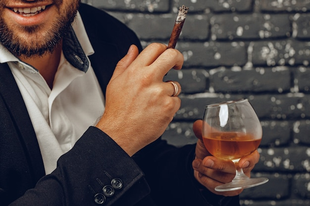 Man holding a glass of whisky and lit cigarette in hands close up photo