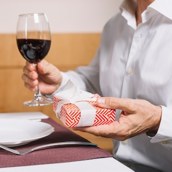 Man holding a glass of wine and gift