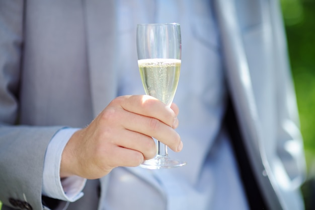 Man holding glass with champagne, focus on glass