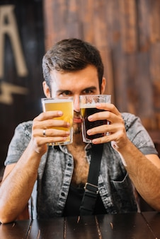 Man holding glasses of beer and rum in bar