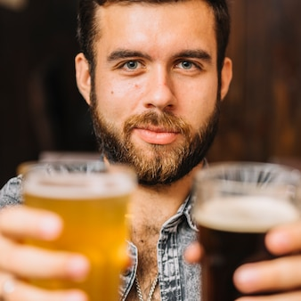 Man holding glasses of beer and rum looking at camera