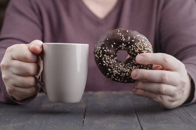 Man holding glazed donut and cup of coffee