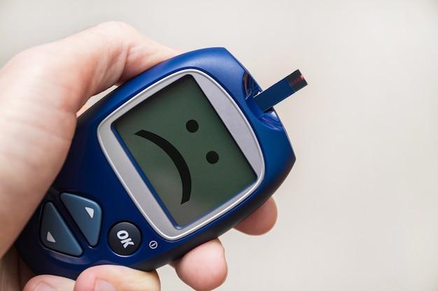 모니터에 슬픈 미소로 테스트 스트립과 혈당 측정기를 들고 남자