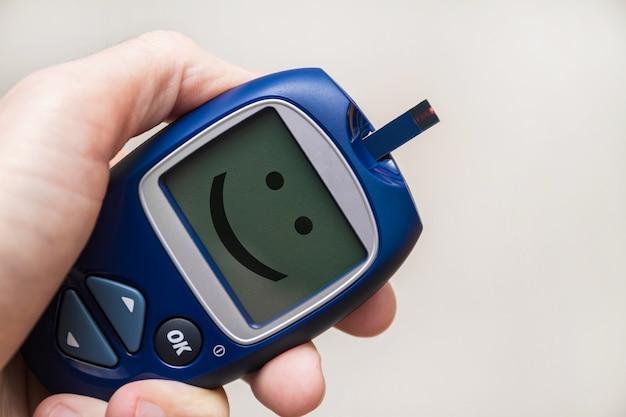 Мужчина держит глюкометр с тест-полоской с улыбкой на мониторе