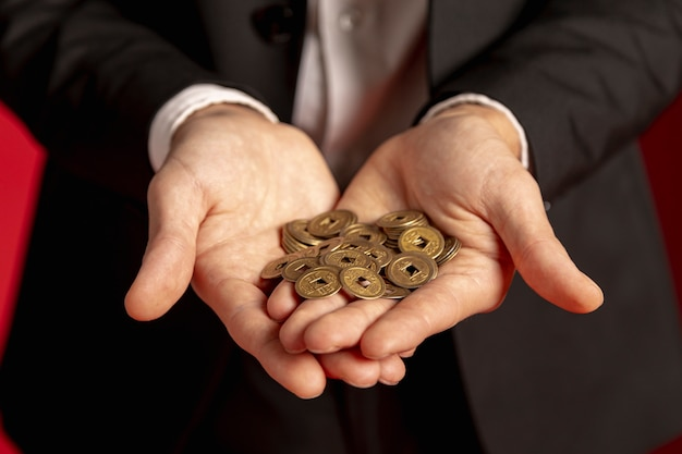 Man holding golden chinese coins in hands for chinese new year