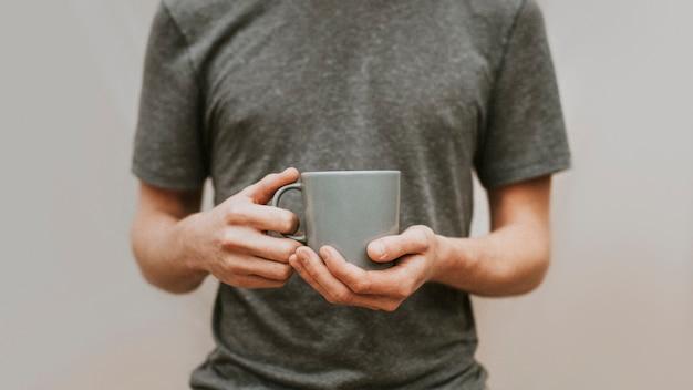 Uomo che tiene una tazza di caffè in ceramica grigia