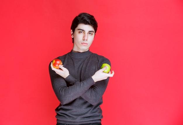 Мужчина держит в руке зеленый мандарин и красное яблоко