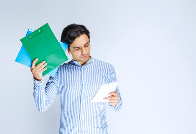 Man holding a green report folder and thinking. high quality photo