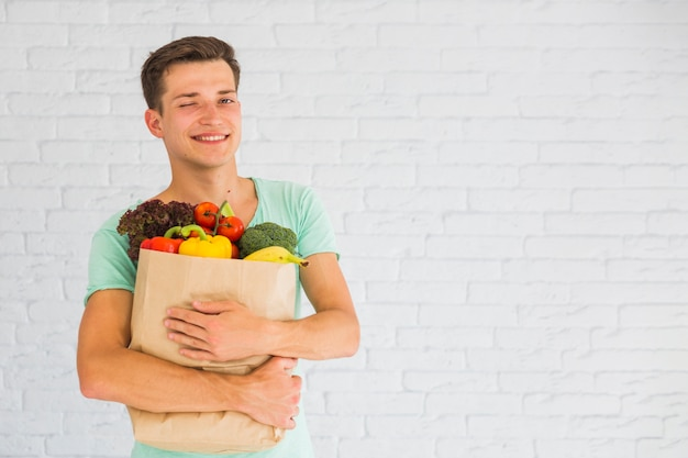 Man holding grocery bag full of fruits and vegetable winking