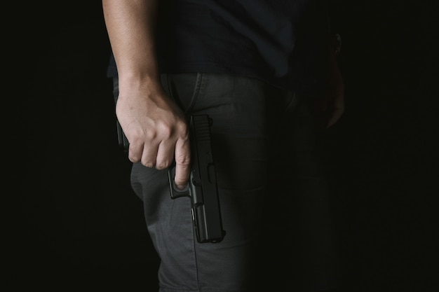 Man holding gun close to the body, killer with 9mm handgun pistol waiting for robbing the victim