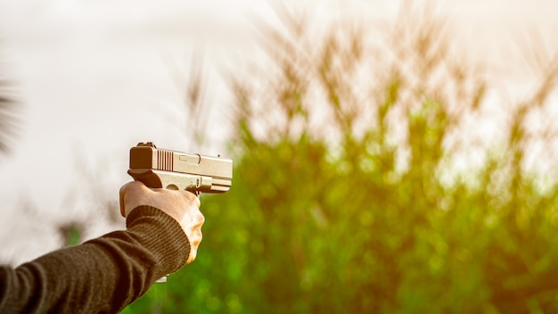 A man holding a gun in hand. - violence and crime concept.