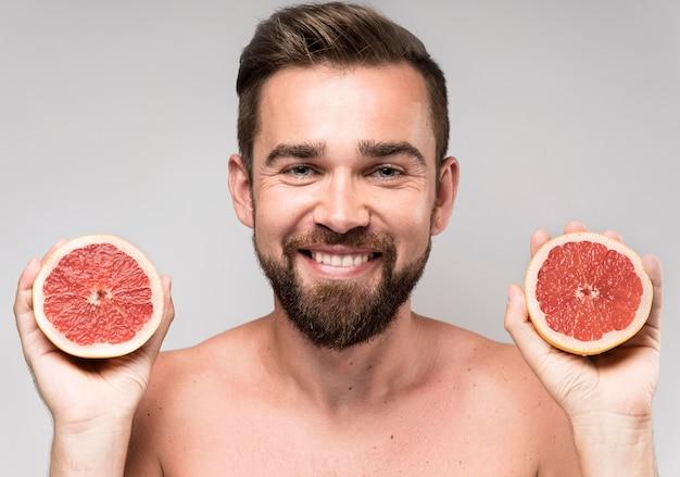 半分のグレープフルーツを持っている男