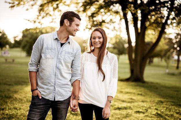 木の近くに立っている女性の手を握って男