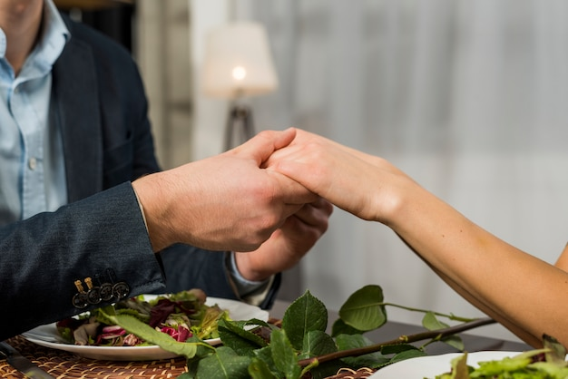 Man holding hand of woman at table with plates