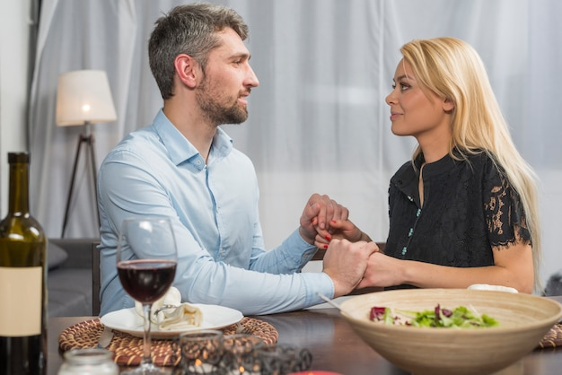 Man holding hands with blond attractive woman at table