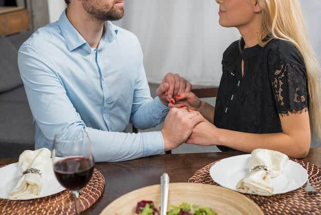 Man holding hands with blond woman at table