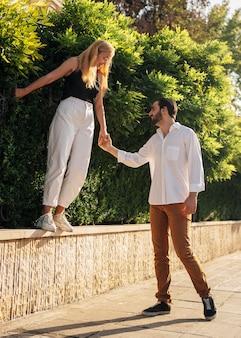 Мужчина держится за руки с женой во время прогулки