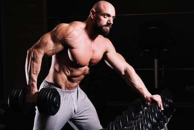 Man holding heavydumbbell near rack