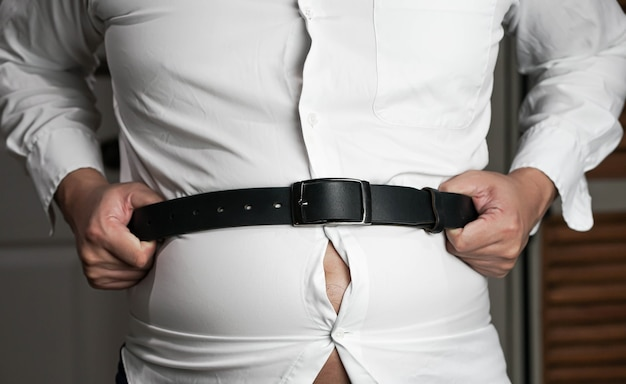 Man holding on his belt and belly, overweight.