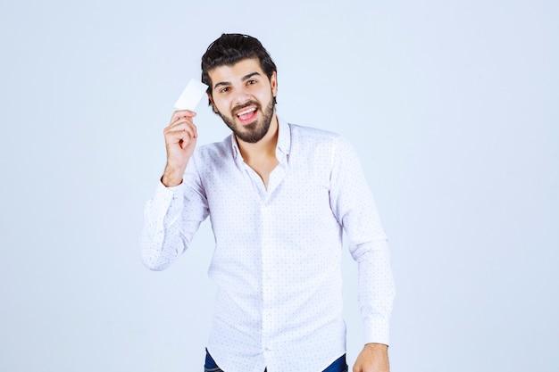 Человек, держащий свою визитную карточку и означающий его успех
