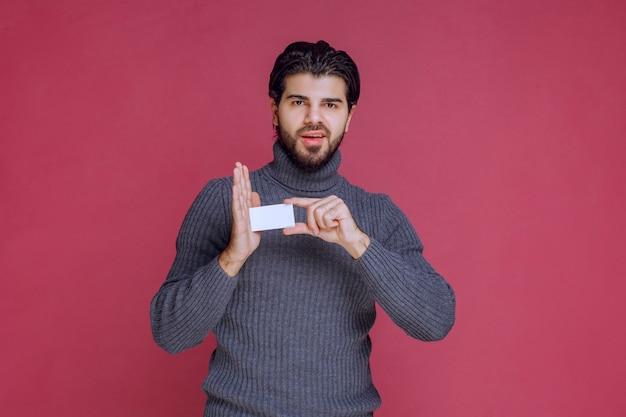 名刺を持って指さしている男。