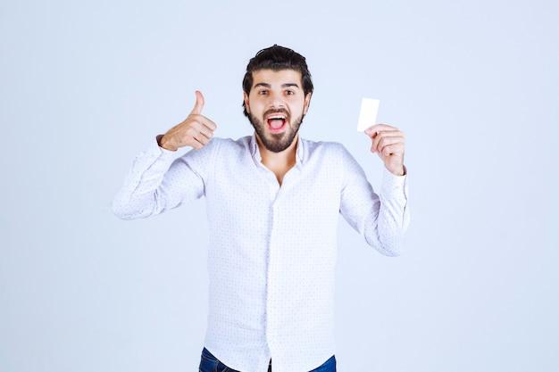 名刺を持って親指を立てる男