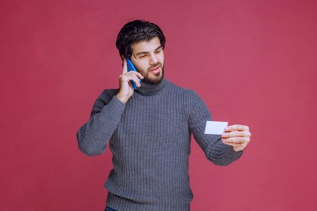 Uomo che tiene il suo biglietto da visita e chiama il numero di contatto su di esso.
