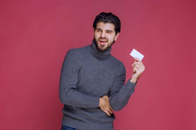 Мужчина держит свою визитную карточку, чувствуя себя очень позитивно и уверенно.