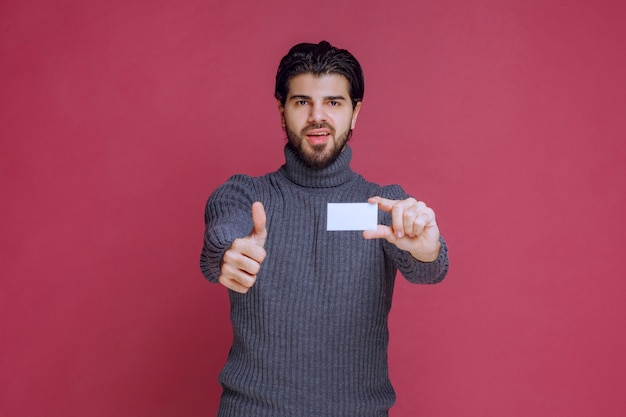 Man holding his business card and makes positive hand sign.