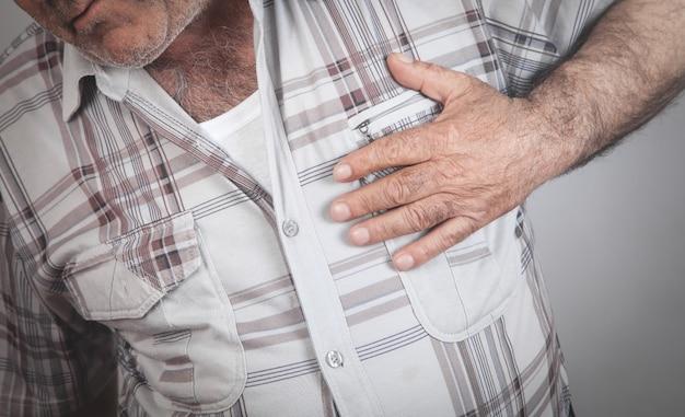 Мужчина держит грудь страдает от сердечного приступа здравоохранение и медицина