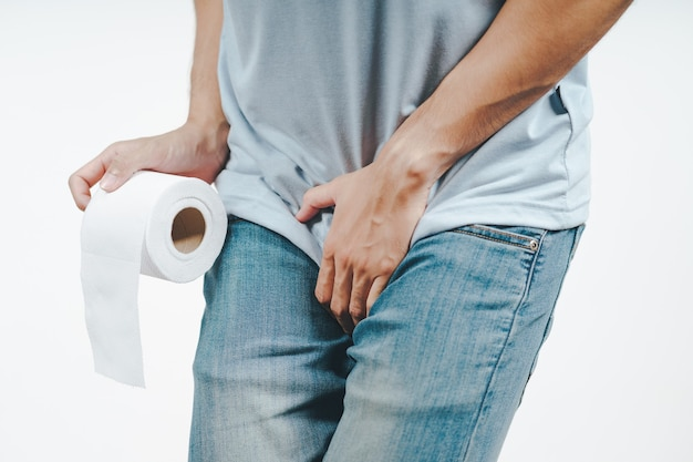 Мужчина, держащий промежность и папиросную бумагу, страдает от диареи, недержания мочи, венерического простатита