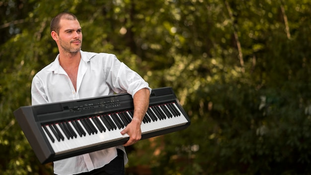 Man holding his digital piano outdoors
