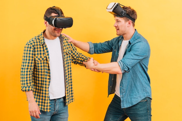 Man holding his friend wearing virtual reality glasses on yellow background
