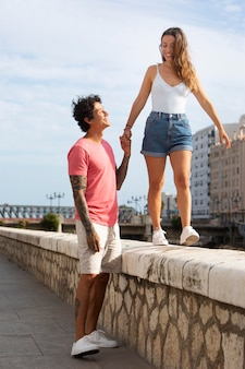 Мужчина держит свою подругу за руку на открытом воздухе