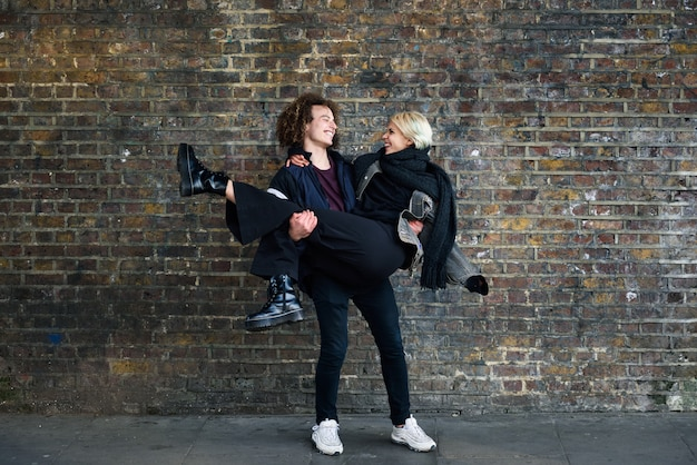 Man holding his girlfriend in his arms in front of a brick wall typical of london