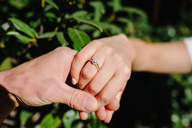 Мужчина держит руку своей подруги. человек делает предложение руки и сердца своей девушке - счастливая пара занимается взявшись за руки. любовь, семья, юбилейное понятие.