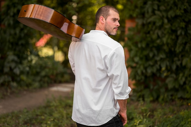 Man holding his guitar on his shoulder from behind shot