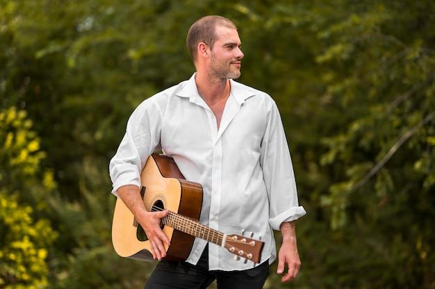 自然の中で彼のギターを握る男