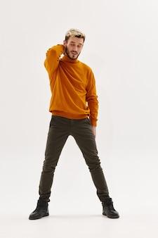 彼の頭の後ろに手を握って男ファッション秋のスタイルの紳士服明るい背景