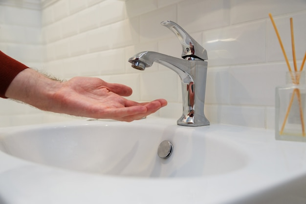 Man holding his hand under opened tap without water. shutdown of water supply for non-payment or during repair work of the central system.