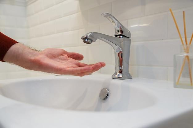 Человек, держащий руку под открытым краном без воды. отключение подачи воды за неоплату или во время ремонтных работ центральной системы.