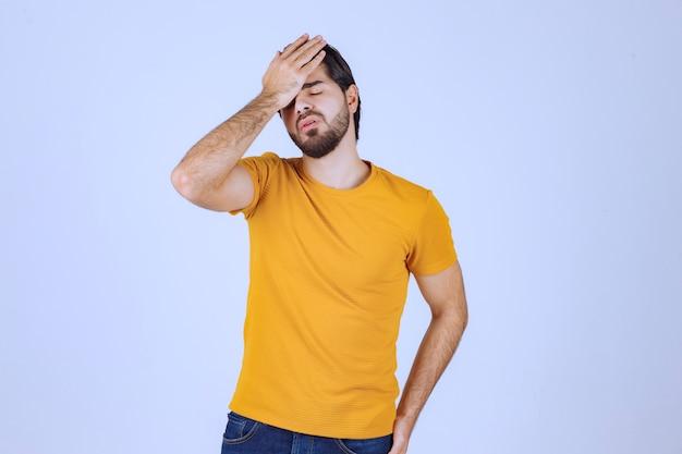 Мужчина держит голову, когда у него болит голова.