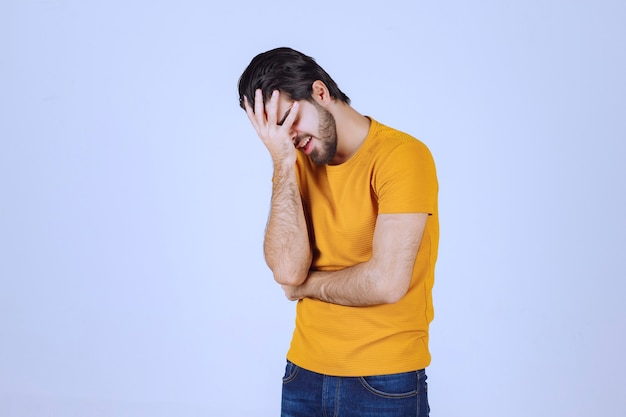 頭痛がするので頭を抱えている男。