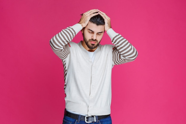 Man holding his head as he is exhausted or has headache.