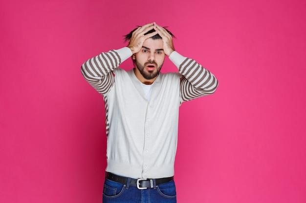 Мужчина держит голову, когда он истощен или болит голова.